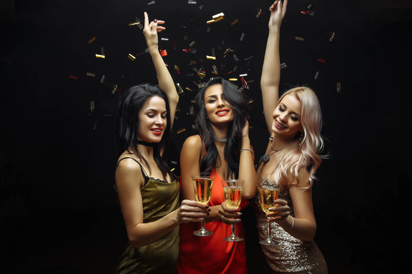 Young attractive women celebrating a party, drinking champagne and dancing